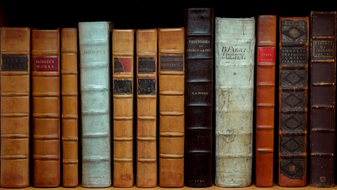 An image of a number of John Adams' books arranged on a shelf.