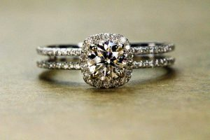 This image shows an engagement ring with a square cut, surrounded by tiny stones. The tiny stones and the large stone are so close together that they look like one big stone.