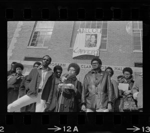 Positive image of a photographic negative showing nine African American standing in front of a building displaying a handmade banner with the partial words Malcol_ Univers_ displayed.