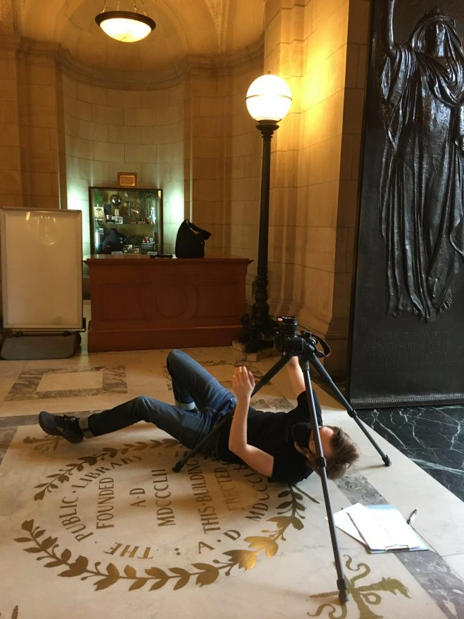 A member of BPL's A/V team films the Lobby ceiling from floor level.