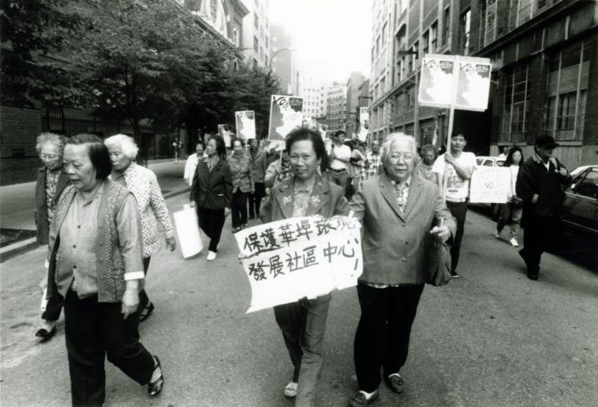 Protesters march in the street; many of them are carrying signs in Chinese text.